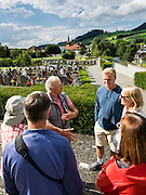 Group of people meet at graveyard of St. Maurice / Mauritius parish church, Appenzell village, Switzerland. Appenzell's Roman Catholic St. Maurice (or Mauritius) parish church was built 1560–84 at Adlerplatz, the heart of Appenzell village, in Switzerland, Europe. Most of the notable buildings in Appenzell were built in the 1500s. Appenzell Innerrhoden is Switzerland's most traditional and smallest-population canton (second smallest by area).