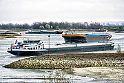 Nederland, the netherlands, Millingen, 29-11-2018 Nog nooit stond het water in de Waal zo laag . Binnenvaartschepen varen ver onder de capaciteit. Door de aanhoudende droogte staat het water in de rijn, ijssel en waal extreem laag . Laagterecord en de laagste officiele stand ooit bij Lobith gemeten. Schepen moeten minder lading innemen om niet te diep te komen . Hierdoor is het drukker in de smallere vaargeul . Door te weinig regenval in het stroomgebied van de rijn is het de waterafvoer extreem weinig . De Waal is het Nederlandse deel van de Rijn en de belangrijkste vaarroute van en naar Rotterdam en Duitsland . Aftakkingen zijn de minder bevaren Nederrijn en IJssel. De levering, aanvoer van vracht, lading,grondstoffen, voor fabrieken en brandstof wordt problematisch. Foto: Flip Franssen