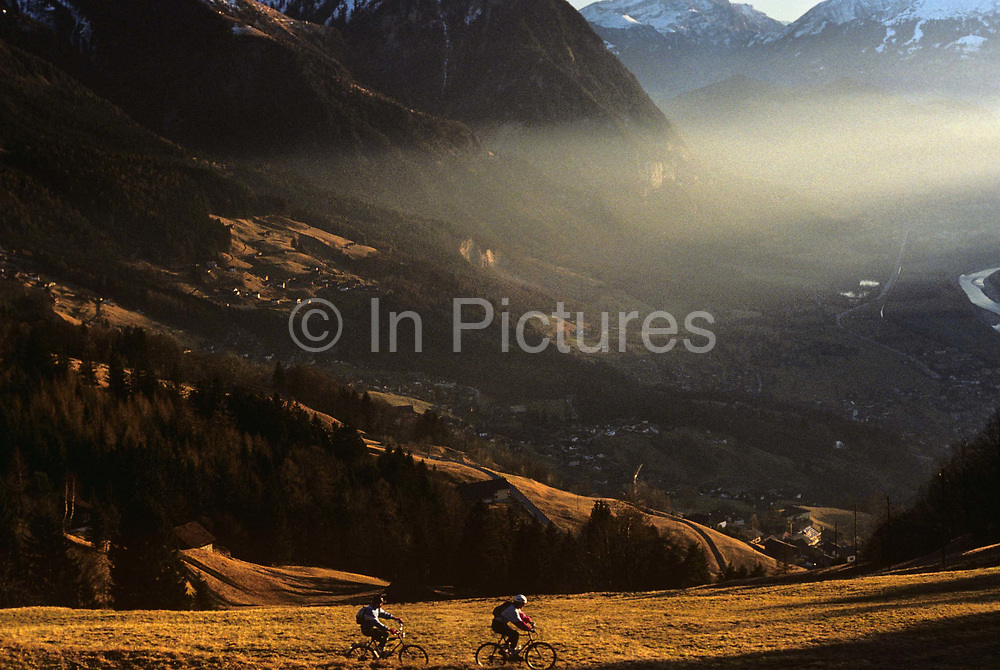 Looking downwards from a high vantage point on a hillside, we see one mountain-biker leading a second cyclist as they traverse across a sunlit mountainside near the hamlet of Masecha in the parish of Triesenberg, Liechtenstein. The late afternoon sun is low across the valley and there is a haze that partly obscures and refracts light over the distant landscape. There is snow on the distant mountain peaks but the countryside has the brown look of a snowless winter. Far off villages and hamlets hug the hillsides and golden light floods the scene. The tiny landlocked Principality of Liechtenstein is bordered by the Alpine countries of Austria and Switzerland and is a winter sports resort, though best known as a tax haven, attracting companies worldwide to register their assets in secrecy.