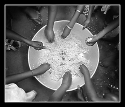 Dembel Jumpora-Dinner-Children eat the staple diet of rice from a communal bowl.  During the end of the dry season, there is little to eat and many villagers will have only one meal of rice each day.