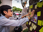 """06 JULY 2015 - BANGKOK, THAILAND: A person puts a """"Post It"""" note in support of arrested university students during a protest at Thammasat University. More than 100 people gathered at Thammasat University in Bangkok Monday to show support for 14 students arrested two weeks ago. The students were arrested for violating orders against political assembly. They face criminal trial in military courts. The students' supporters are putting up """"Post It"""" notes around Bangkok and college campuses up country calling for the students' release.   PHOTO BY JACK KURTZ"""