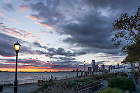 Tourists and residents enjoy a Fall sunset along one of Manhattan's shorelines. The magnificent sunset and cityscape combine to create a beautiful travel destination in Battery Park.