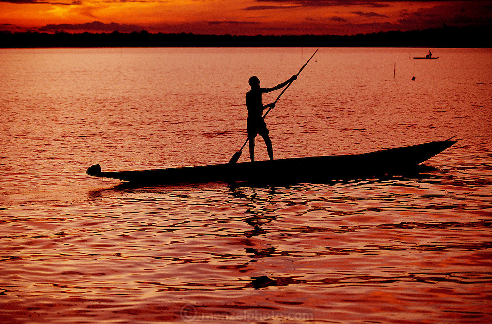 Fisherman in a dugout canoe at sunset on the Pomats River at Sawa Village, in the Asmat Swamp, a large, steamy hot tidal swamp. Irian Jaya, Indonesia. Image from the book project Man Eating Bugs: The Art and Science of Eating Insects.