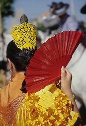 "Europe, Spain, Andalucia, Sevilla, woman in flamenco dress holding fan during ""Feria de Abril"" festival, held annually in April"