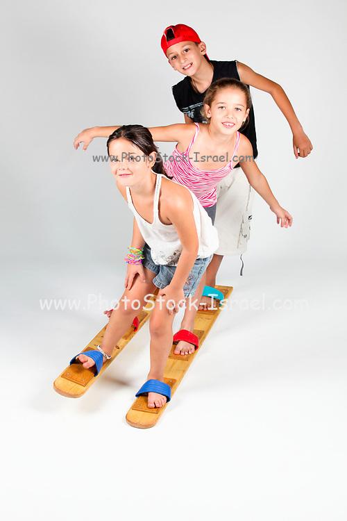 Indoor playground  3 children aged 8-12 attempt to walk together on wooden walking skies On white Background