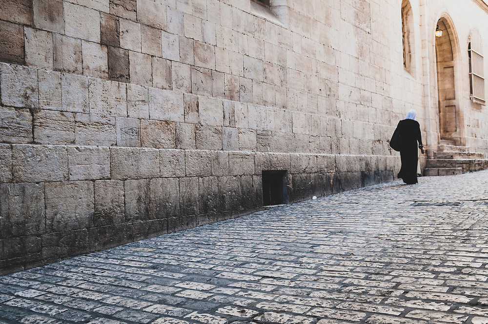 A Palestinian woman walks on the Via Dolorosa in the Muslim Quarter of Jerusalem's Old City on October 20, 2010.