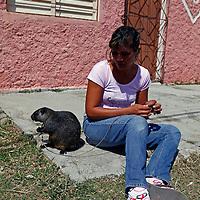 Central America, Cuba, Caibarien. Cuban girl and her pet Cuban Hutia, the largest endemic mammal on the island of Cuba.