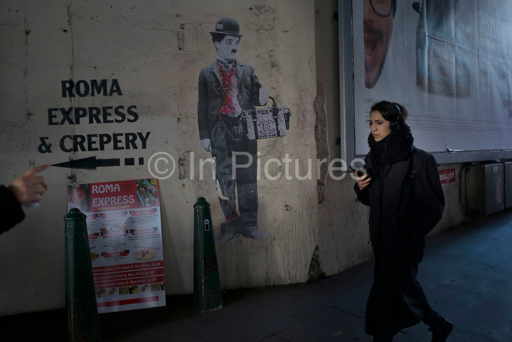 Street art of Charlie Chaplin interacts with passers by and other visual advertising under a bridge in London Bridge, UK. People juxtappose the artwork of the famous silent movie star as their faces and shapes work alongside him.