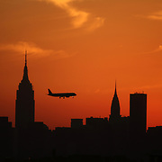 NEW YORK, NEW YORK - SEPTEMBER 26:   An airplane flies past the Manhattan skyline at sunset showing the Empire State Building, (highest point, left) and the Chrysler building shot from Citi Field Stadium during the Atlanta Braves Vs New York Mets MLB regular season game at Citi Field, Flushing, Queens, on September 26, 2017 in New York City. (Photo by Tim Clayton/Corbis via Getty Images)
