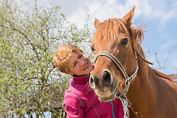 Woman showing affection to her horse, Bavaria, Germany