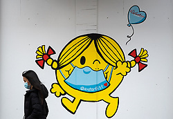 A woman wearing a face mask walks past artwork of author and illustrator Roger Hargreaves' 'Little Miss Sunshine' character wearing a face mask, painted on the outside of a boarded up business in downtown Vancouver, BC, Canada on Sunday, April 19, 2020. TPhoto by Darryl Dyck/CP/ABACAPRESS.COM