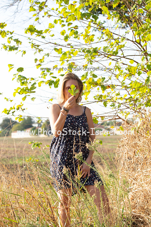 Portrait of a blond woman holds a fresh leaf infront of her face
