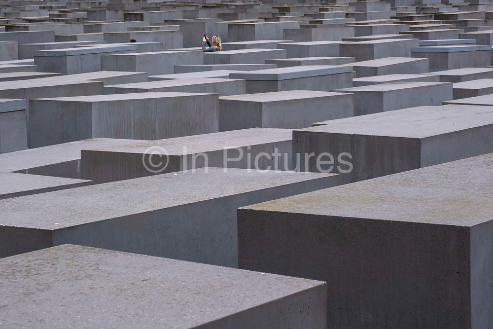 A woman taking a picture inside the Holocaust memorial, a memorial on 11th October 2019 in Berlin, Germany to the Jewish victims of the Holocaust designed by architect Peter Eisenman and engineer Buro Happold. It consists of 2,711 concrete slabs  covering a 19,000-square-metre site arranged in a grid pattern. Berlin. Germany.