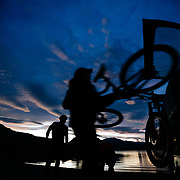 """Chris """"Canguro"""" Theobald loading bikes into his pickup truck at sunset. Riding the singletrack of Lake Sophia park outside of Torres del Paine National Park in Chile."""