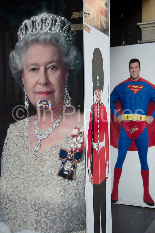 Queen Elizabeth II poster in a juxtaposition next to one of Superman and a member of the Guards wearing a bear skin at Leicester Square in London, England, United Kingdom.