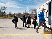 """17 MARCH 2020 - DES MOINES, IOWA: GRADY FOX, right, with the Boys & Girls Clubs and working with the Des Moines Area Religious Council (DMARC) walks back to the food distribution trailer in the parking lot of Carver Elementary School in Des Moines after giving bags of food to a family. Des Moines Public Schools are closed for at least 30 days because of the Coronavirus outbreak. Des Moines area religious organizations and food banks are working together to bring free food to children in at risk communities. Volunteers and workers are practicing """"social distancing"""" by leaving the food packages on the pavement and recipients pick up the packages. Tuesday, the Governor of Iowa ordered all restaurants and bars to close or go to take out only. The Iowa Department of Public Health has urged all public buildings, like libraries and schools, to close, and all schools in Iowa are closed for at least 30 days.     PHOTO BY JACK KURTZ"""