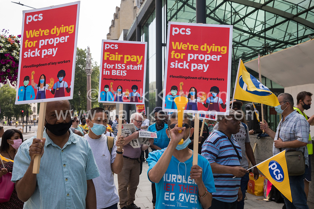 Members of the PCS trade union working for the outsourced contractor ISS stand on the picket line outside their workplace at the Department for Business, Energy and Industrial Strategy (BEIS) on the second day of a 3-day strike on 20th July 2021 in London, United Kingdom. The striking cleaners, security guards and other support staff at the government department are demanding an end to low pay, improved working conditions, bonuses for having worked through lockdown, annual leave from last year and a Covid return-to-work protocol.