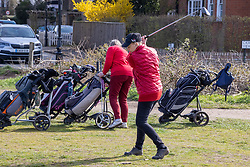 """© Licensed to London News Pictures. 29/03/2021. London, UK. A Golfer practices while queuing up to tee off on Wimbledon Common golf course, South West London as the """"Stay at Home"""" government advice ends. From today, Monday 29 March, the """"Stay at Home"""" advice will end with people being allowed to meet up within the """"rule of six"""". Playing golf, tennis and organised outdoor sports will also be allowed as England starts to unlock after a year of Covid-19 restrictions. Photo credit: Alex Lentati/LNP"""