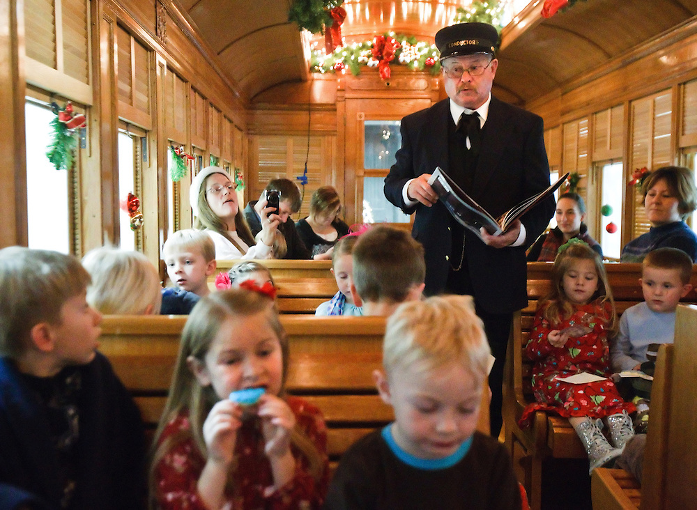 """Conductor Larry Roberts read from """"The Polar Express"""" by Chris Van Allsburg as Emma Carlson, 6, of Columbus, takes a bite of her cookie inside the Florence and Cripple Creek boarding car during the North Pole Express event Saturday at the Stuhr Museum.  (Independent/Matt Dixon)"""