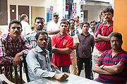 16 DECEMBER 2012 - SINGAPORE, SINGAPORE:  Indian men stand in Perak Street in the Little India section of Singapore to watch a cricket game on a TV set in an Indian restaurant. .     PHOTO BY JACK KURTZ