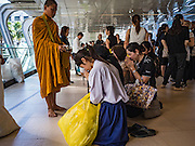 """29 NOVEMBER 2016 - BANGKOK, THAILAND:  A Buddhist monk prays for people who donated food during a special """"tak bat"""" or merit making ceremony in the Ratchaprasong skywalk of the Bangkok BTS system. The tak bat was to honor Bhumibol Adulyadej, the Late King of Thailand. Food and other goods were given to the monks, who in turn gave the items to charities that will distribute them to Bangkok's poor. More than 100 Buddhist monks participated in the merit making ceremony. The ceremony was organized by the merchants in the Ratchaprasong Intersection, which includes some of Bangkok's most upscale shopping centers.     PHOTO BY JACK KURTZ"""
