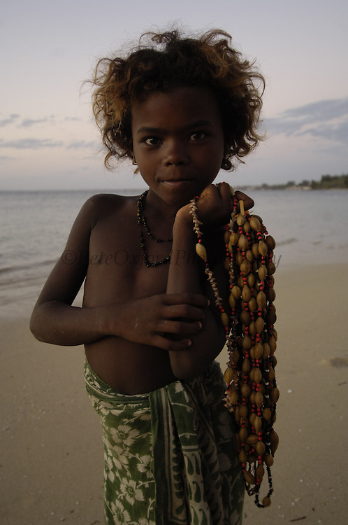 Child selling necklaces on the beach made from seeds and shells found locally.<br />Mangily, near Ifaty.  South-western MADAGASCAR