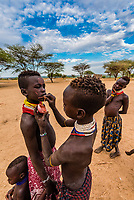 Teenaged Kara tribe girls having their faces painted, Omo Valley, Ethiopia.