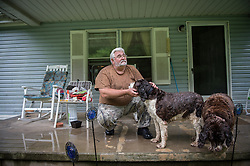 "Charles Bella of Blair, West Virginia plays with his dog outside his home. ""I worked on the mountaintop mine,"" Bella said. ""That comes back and haunts me to this day. I was part of destroying my own community."" Mountaintop Removal is a method of surface mining that literally removes the tops of mountains to get to the coal seams beneath. It is the most profitable mining technique available because it is performed quickly, cheaply and comes with hefty economic benefits for the mining companies, most of which are located out of state. It is the most profitable mining technique available because it is performed quickly, cheaply and comes with hefty economic benefits for the mining companies, most of which are located out of state. Many argue that they have brought wage-paying jobs and modern amenities to Appalachia, but others say they have only demolished an estimated 1.4 million acres of forested hills, buried an estimated 2,000 miles of streams, poisoned drinking water, and wiped whole towns from the map. © Ami Vitale"
