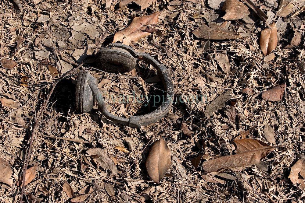 01 October, 05.  New Orleans, Louisiana. Lower 9th ward. Hurricane Katrina aftermath. <br /> The remnants of the lives of ordinary folks, now covered in mud as the flood waters recede. A pair of headphones lies on the dead grass.<br /> Photo; ©Charlie Varley/varleypix.com