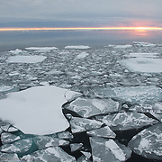The sun sets over broken chunks of newly forming ice in the Arctic Ocean.