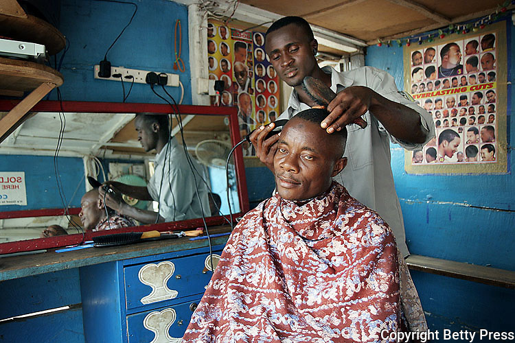 Man is getting his hair cut at the Top Class Barbing Shop.  Sign on back wall shows a variety of hair styles called  everlasting cuts.