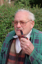 Elderly man smoking a pipe and wearing glasses,