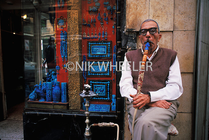 Egyptian man smokes narguileh water pipe outside jewelry store in Cairo, Egypt