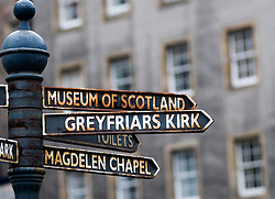 Signs pointing out directions to several historical sights in Grassmarket district of Edinburgh Scotland
