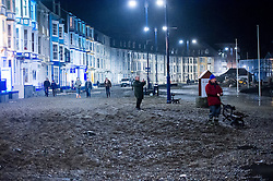 © London News Pictures. 08/02/2016. Aberystwyth, UK.<br /> Huge amounts of debris washed on the the promenade as members of the public watch as the evening  high tide reaches its peak and waves continue to hit the sea defences at Aberystwyth on the west Wales coast. Photo credit: Keith Morris/LNP