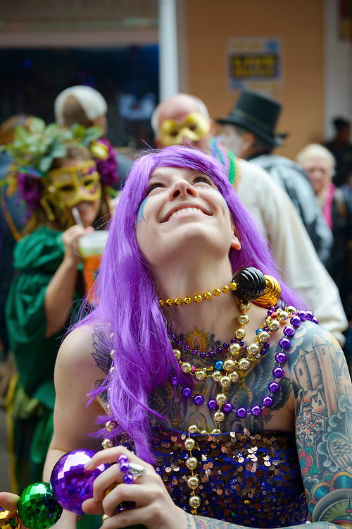A young woman catches beads on Bourbon Street in New Orleans during Mardi Gras 2013.