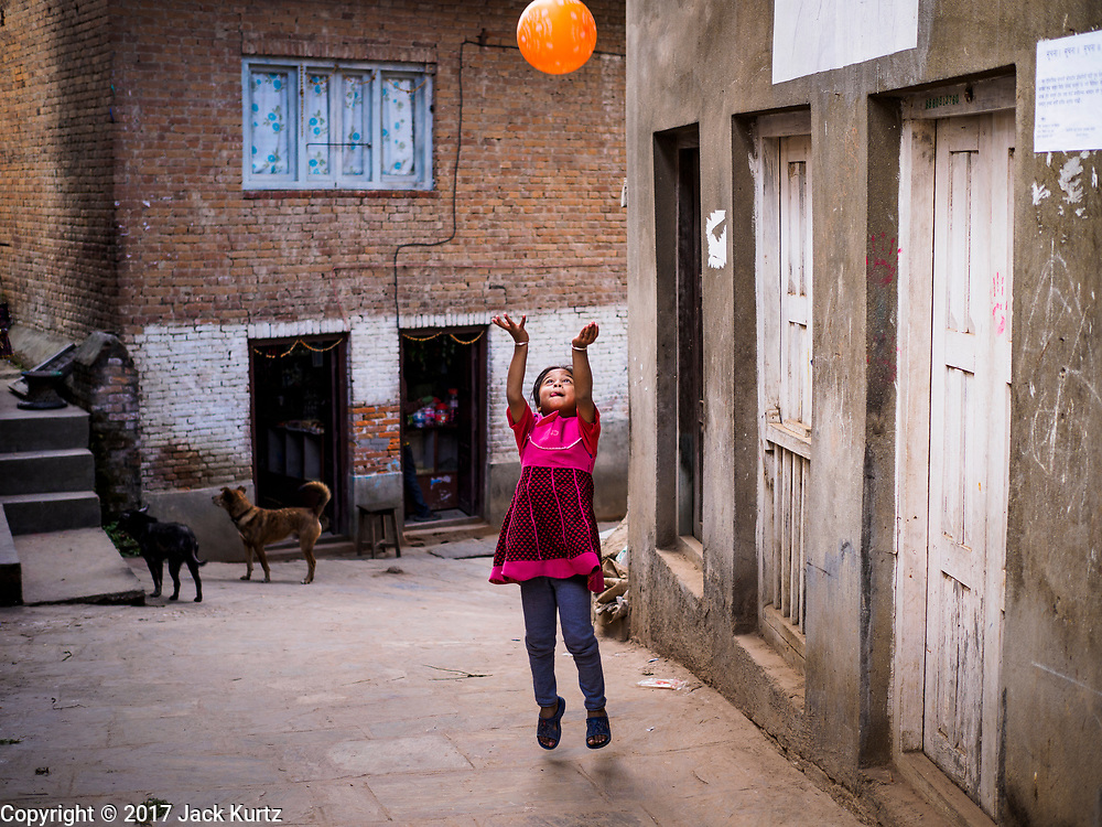 14 MARCH 2017 - BUNGAMATI, NEPAL: A child plays on a street Bungamati. Bungamati, a community of wood carvers and artisans, used to be a stop on the tourist trail of the Kathmandu valley but since the 2015 earthquake few tourists visit the community. Recovery seems to have barely begun nearly two years after the earthquake of 25 April 2015 that devastated Nepal. In some villages in the Kathmandu valley workers are working by hand to remove ruble and dig out destroyed buildings. About 9,000 people were killed and another 22,000 injured by the earthquake. The epicenter of the earthquake was east of the Gorka district.            PHOTO BY JACK KURTZ