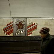 KIEV, UKRAINE - February 25, 2014: A woman passes by a soviet era mural in Arsenalia Metro station, Kiev. CREDIT: Paulo Nunes dos Santos