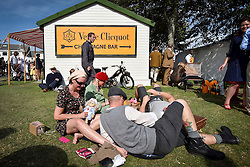 © licensed to London News Pictures.12/09/2015<br /> Goodwood Revival Weekend, Goodwood, West Sussex. UK.<br /> The Goodwood Revival is the world's largest historic motor racing event. Competitors and enthusiasts dress in period fashions recreating the glorious days of the race circuit.<br /> Pictured. Racegoers relax at the champagne bar.<br /> <br /> Photo credit : Ian Whittaker/LNP