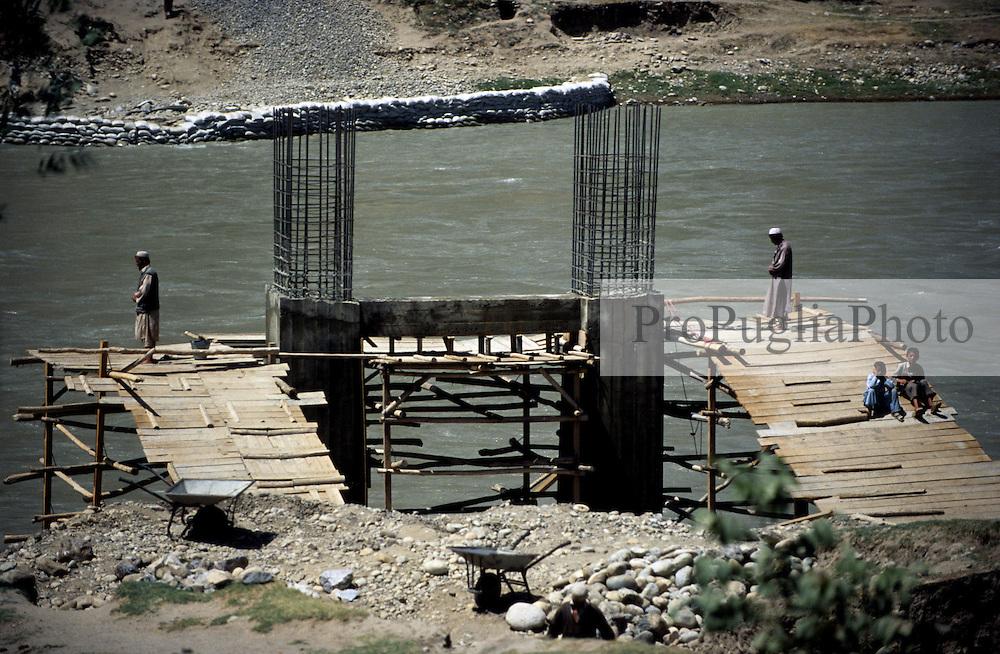 FAIZABAD, 27 July 2005..KOKCHA RIVER....A new bridge is under construction, ..Muslims are performing 'Salat'