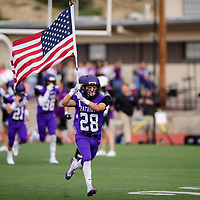 Brandon Ransom of the Miyamura Patriots carrries the flag as the team takes the field before their game against the Aztec Tigers, Friday, August 24, 2018 at Angelo DiPaolo Stadium in Gallup.
