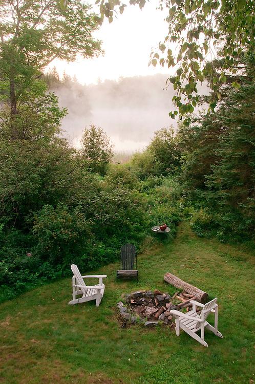 Adirondack chairs around a fire pit at the Republic Island Cottage near Republic Michigan.