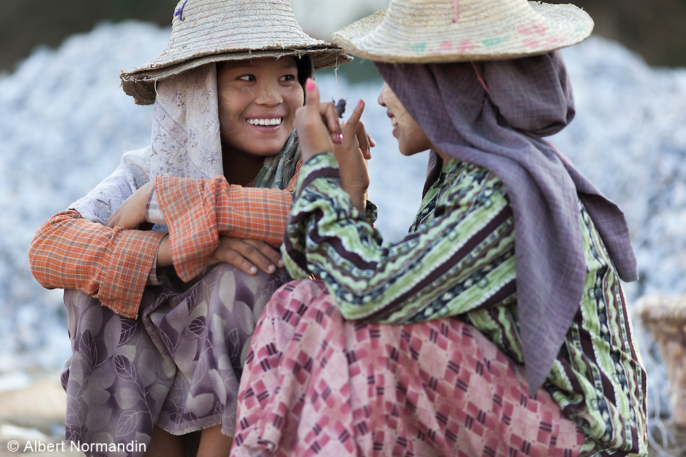 Two young worker ladies taking a break from work, talking and laughing, Ayeryarwady River Jetty, Mandalay