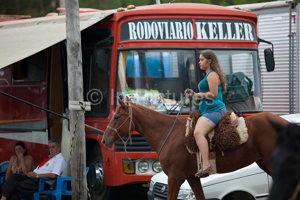 Young Brazilian Gaucha cowgirl female, riding a horse. Gaucho cowboy Rodeo, Flores de Cunha, Rio Grande do Sul.