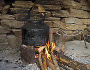 A teapot heats over the flames of a wood fire at Gurung Cottage, at Ghandruk in Nepal.