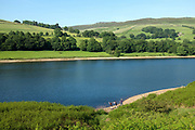 A family throwing stones into the water at Ladybower Reservoir, Derbyshire on 17 June 2017