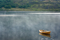 Lone wooden boat floating on Loch Maree, Wester Ross Scotland