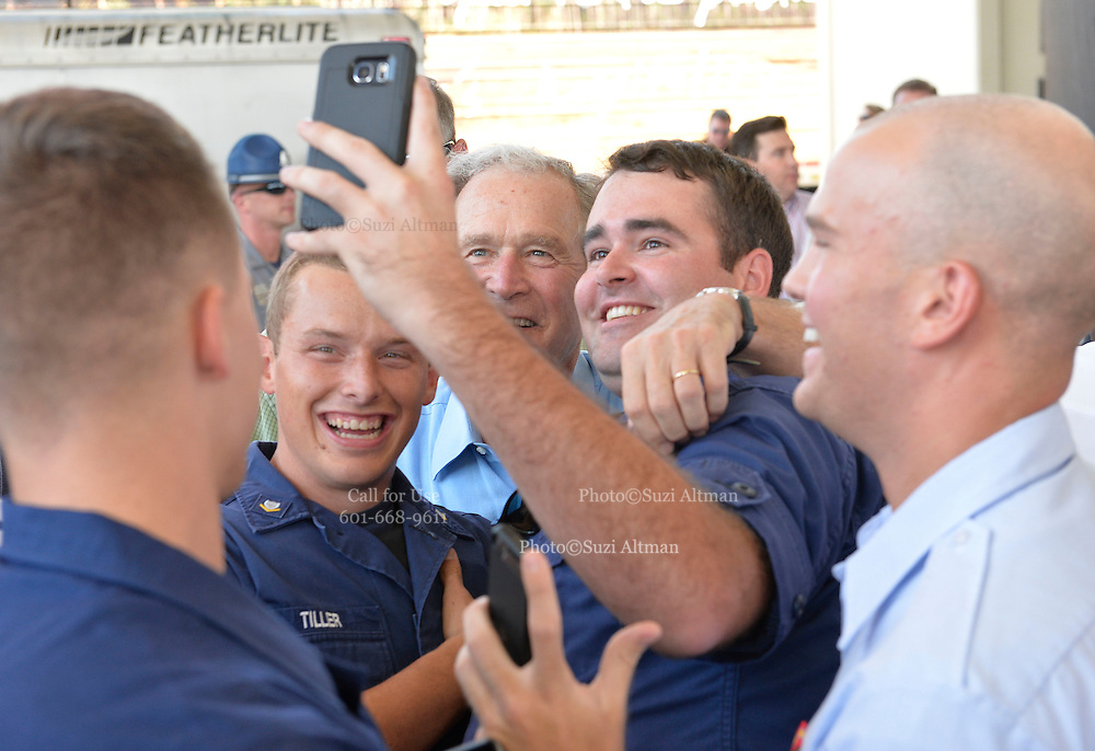"""Gulfport, MS 8/28/15 President Bush poses for """"selfies"""" with  Mississippi first responders during the 10th Anniversary Hurricane Katrina event in Gulfport. Mississippi. Governor Phil Bryant checks the morning papers as he waits for  the 10th Anniversary Hurricane Katrina event. to begin. President George Bush joined Mississippi Governor's Haley Barbour and Governor Phil Bryant  for a first responders event to commemorate the 10th Anniversary of Hurricane Katrina in Gulfport Mississippi. Photo ©Suzi Altman"""