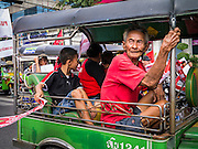 "10 DECEMBER 2012 - BANGKOK, THAILAND:  An elderly Red Shirt rides in a tuk-tuk (three wheeled taxi) during a protest for constitutional reform on Ratchadamnoen Avenue in Bangkok Monday. The Thai government announced on Monday, which is Constitution Day in Thailand, that will speed up its campaign to write a new charter. December 10 marks passage of the first permanent constitution in 1932 and Thailand's transition from an absolute monarchy to a constitutional monarchy. Several thousand ""Red Shirts,"" supporters of ousted and exiled Prime Minister Thaksin Shinawatra, motorcaded through the city, stopping at government offices and the offices of the Pheu Thai ruling party to present demands for a new charter.      PHOTO BY JACK KURTZ"