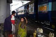 Patti-Das and his wife Leela get dressed piece of waste ground beneath a flyover near Okhla station as a train passes and a passenger shouts abuse at them. New Delhi, India. New Delhi, India